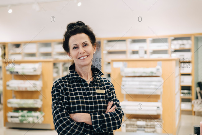 Portrait of smiling saleswoman with arms crossed standing in store