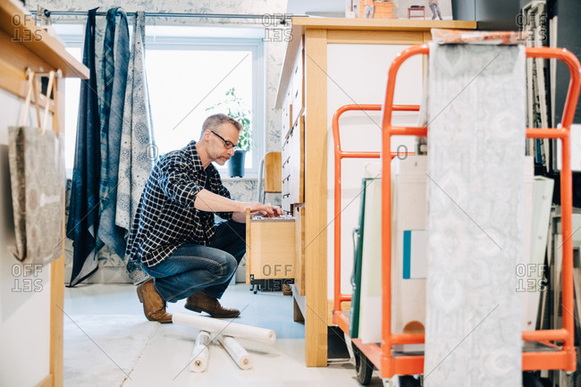 Full length of salesman arranging wallpaper in drawer