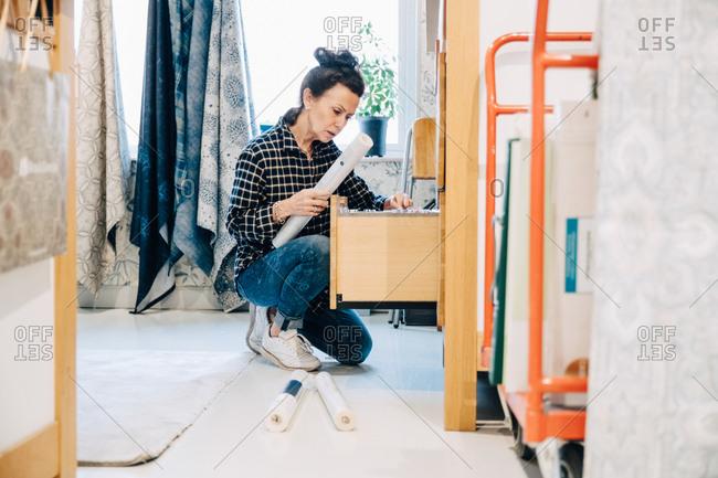 Full length of saleswoman arranging wallpaper in drawer