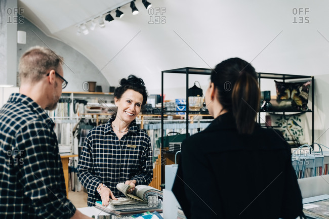 Smiling saleswoman showing wallpaper sample to customer in store