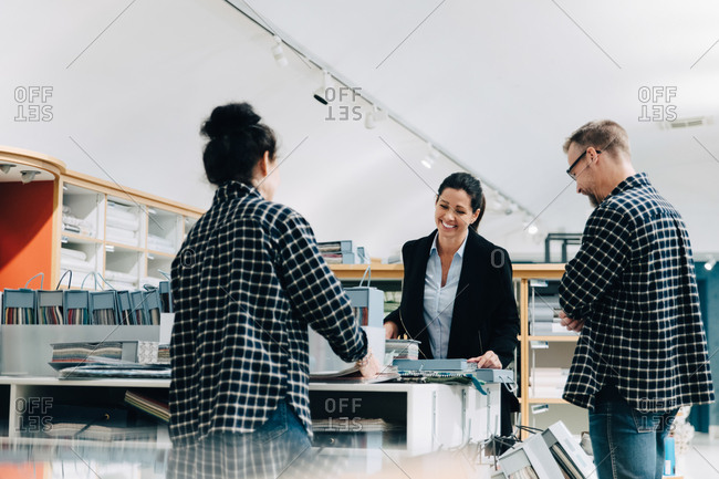 Sales employees assisting female customer in store