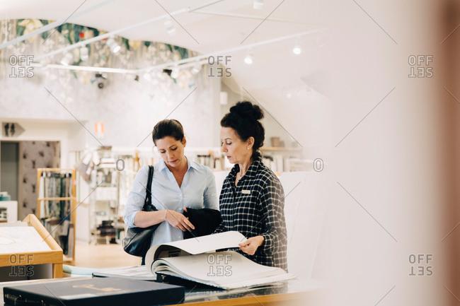 Saleswoman assisting female customer choosing wallpaper sample in store
