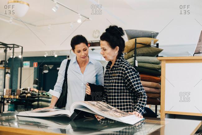 Woman assisting customer choosing wallpaper sample in store