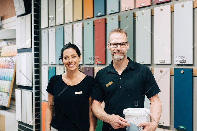 Portrait of smiling coworkers standing against multi colored wall in store