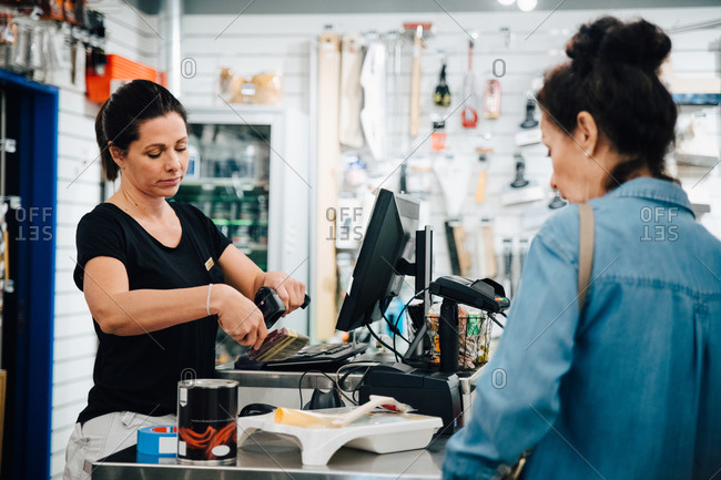 Cashier scanning paint brush while customer standing at checkout counter in hardware store