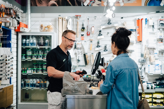 Female Customer talking with shop owner at checkout counter in store