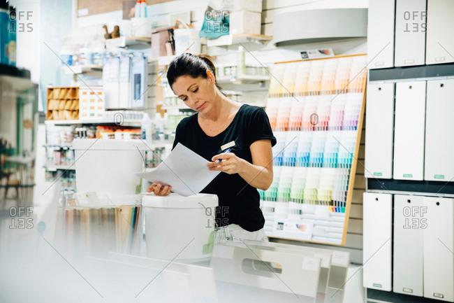 Female employee reading document at hardware store