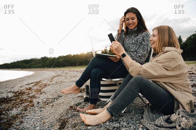 Happy friends looking at smart phone while sitting on shore at beach against sky