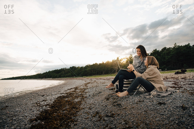 Female friends looking at mobile phone while sitting together at beach during sunset