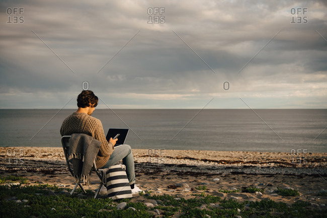 Mid adult man using laptop and mobile phone while sitting on sea shore at beach against sky