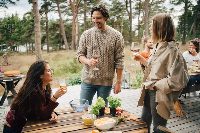 Smiling friends enjoying drinks while talking during garden party in yard