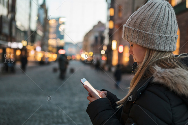 Teenage girl wearing knit hat text messaging on smart phone in city during sunset