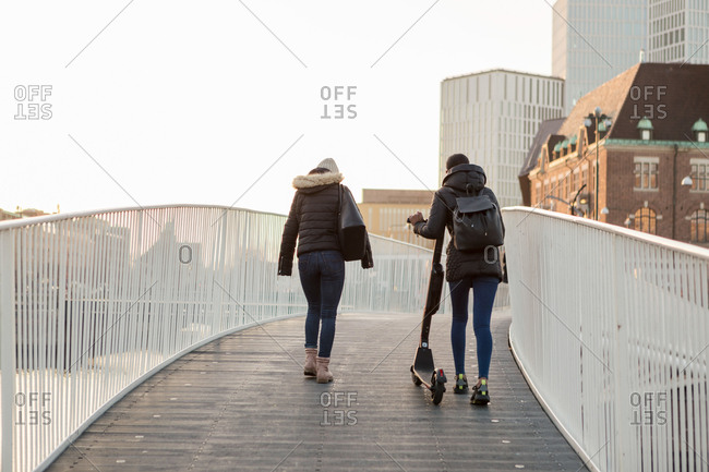 Rear view of female friends walking with e-scooter on bridge in city
