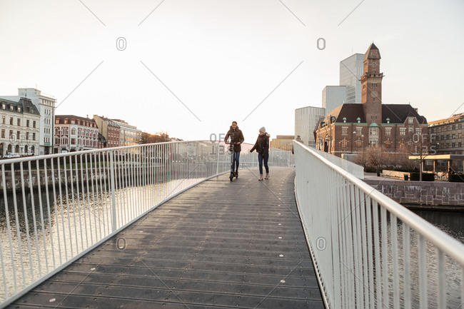 Teenage girl walking with friend riding push scooter on bridge in city against clear sky
