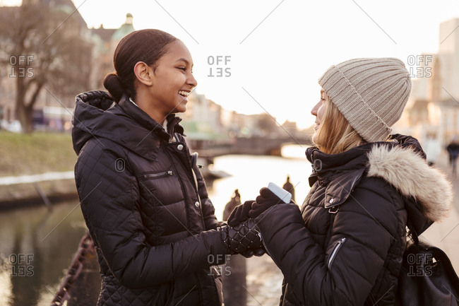 Happy female friends holding hands while talking in city during winter