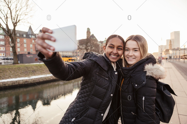 Teenage girl taking selfie with friend on smart phone against canal in city