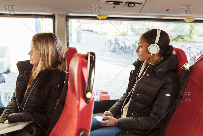 Teenage girl listening music through headphones and female looking through window while traveling in bus