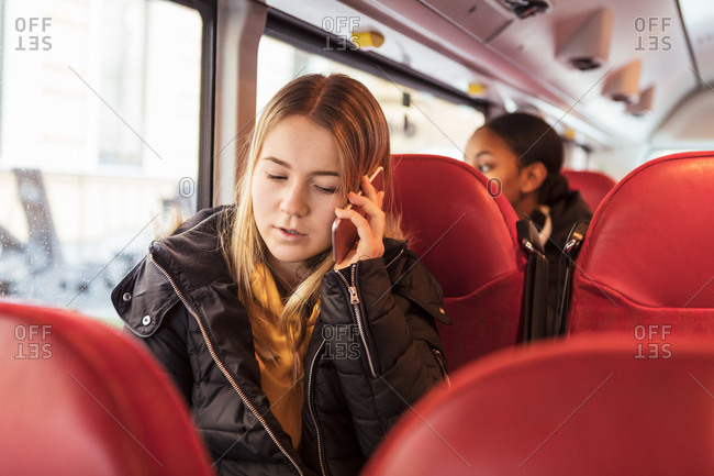 Teenage girl talking on smart phone while sitting in bus