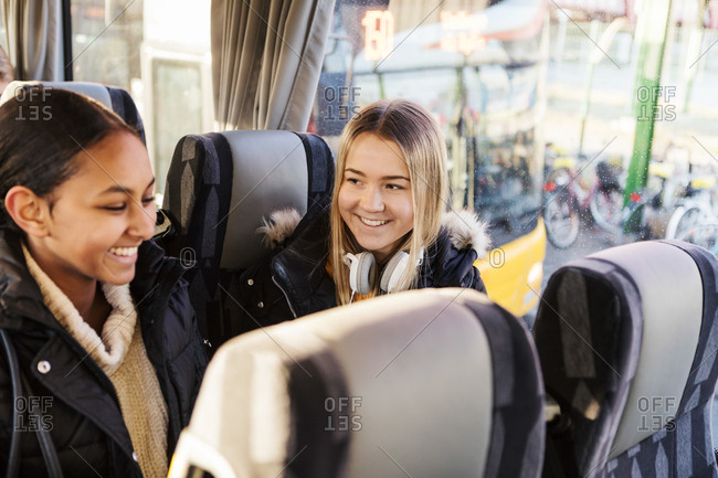 Smiling female friends traveling together in bus at city