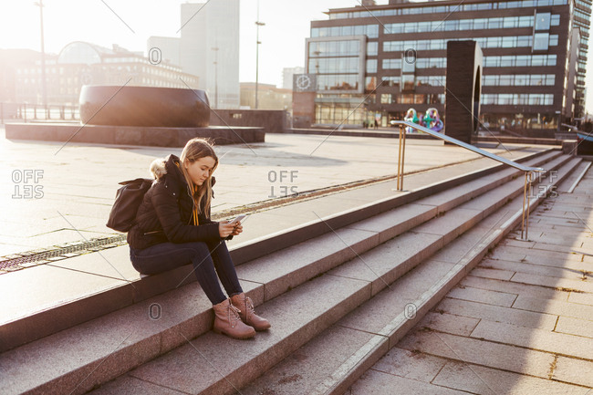 Full length of teenage girl using mobile phone while sitting on steps in city