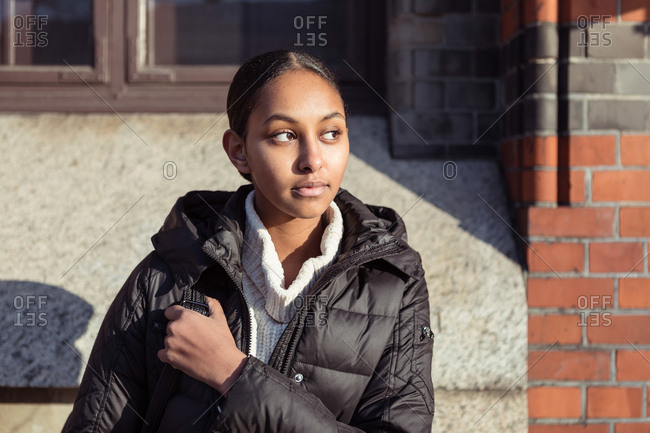 Thoughtful teenage girl wearing jacket looking away while sitting against wall