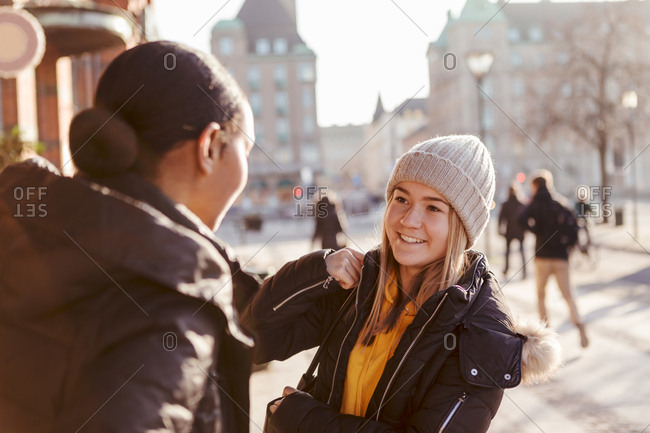 Smiling teenage girl talking to friend in city during winter