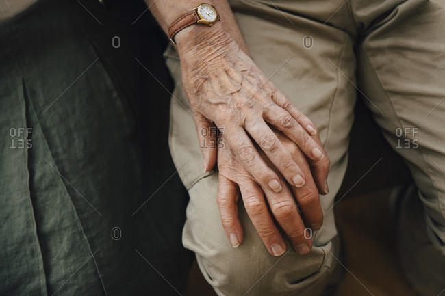 Midsection of retired senior couple holding hands sitting at nursing home
