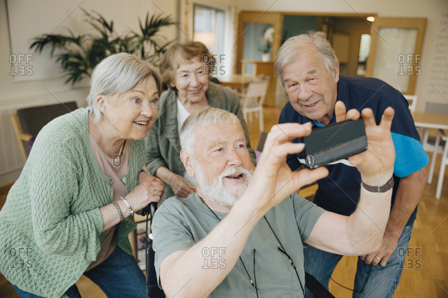 Disabled senior man taking selfie with friends at retirement home