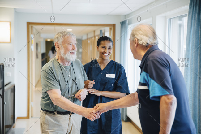 Senior man arm in arm with female nurse while giving friend handshake in alley at nursing home