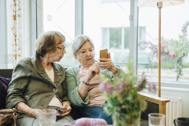 Elderly woman using mobile phone while sitting with female friend on sofa against window at retirement home