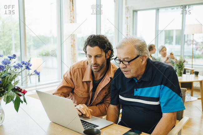Man assisting grandfather using laptop at dining table in retirement home
