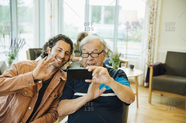 Senior man and grandson video conferencing on smart phone at elderly nursing home