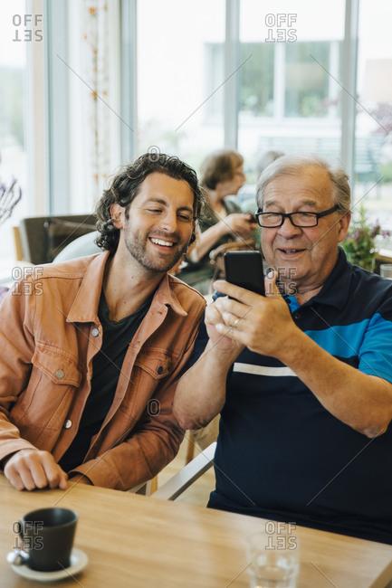 Senior man taking selfie with grandson while sitting at dining table in elderly nursing home