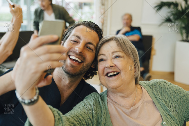 Smiling senior woman taking selfie with male healthcare worker while sitting at retirement home