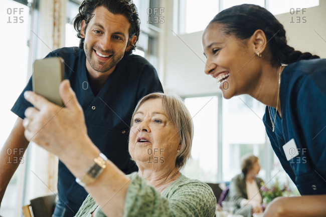 Senior woman taking selfie with smiling male and female nurses at retirement home