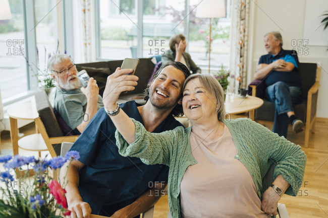 Smiling senior woman taking selfie with male nurse while sitting at retirement home