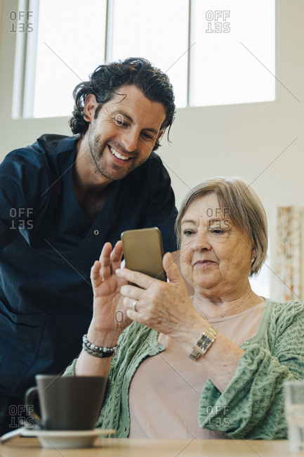Smiling male caregiver assisting senior woman using smart phone in nursing home