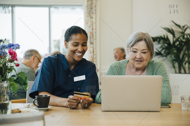 Smiling female caregiver assisting senior woman doing online shopping with credit card and laptop in nursing home