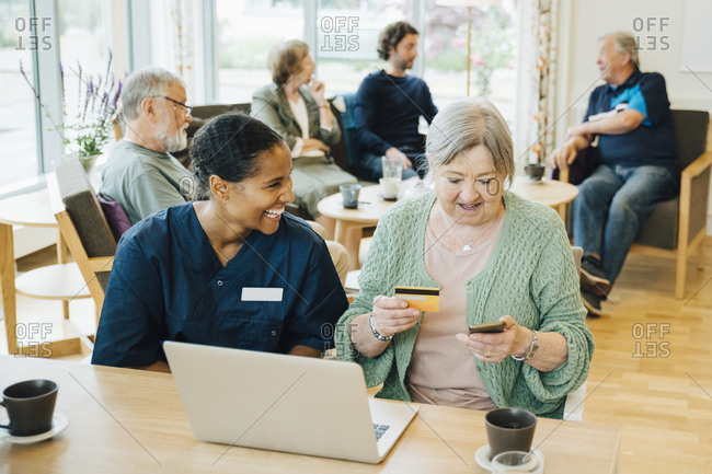 Cheerful female healthcare worker sitting by senior woman doing online shopping with credit card and smart phone in nursing home