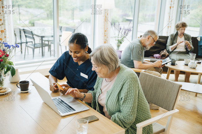 Smiling female healthcare worker assisting senior woman doing online shopping with credit card and laptop in nursing home