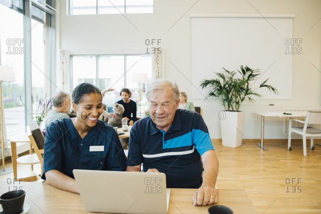 Smiling young female healthcare worker assisting senior man in using laptop at dining table