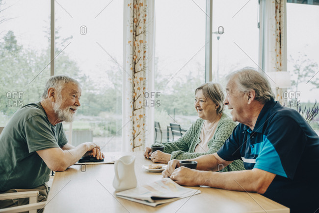 Retired senior friends talking while sitting at dining table in nursing home