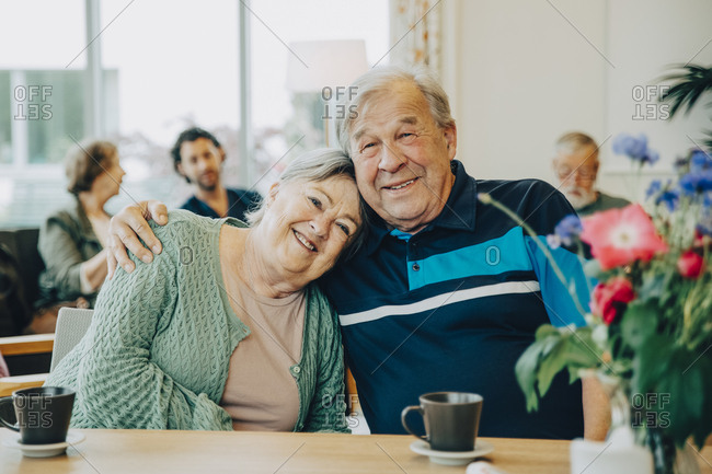 Portrait of elderly senior friends sitting with arm around at dining table in nursing home