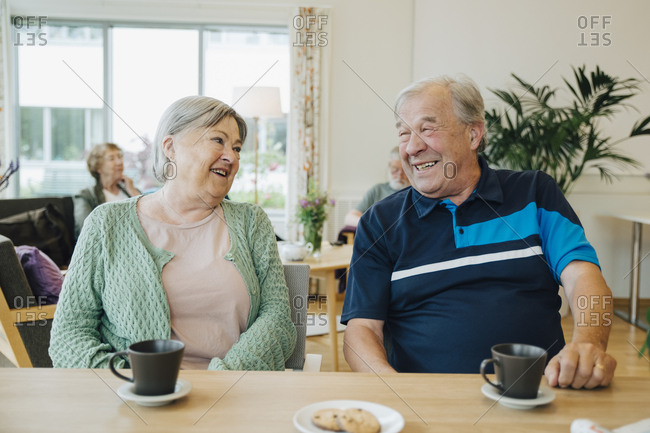 Smiling elderly senior friends talking while sitting at dining table in nursing home