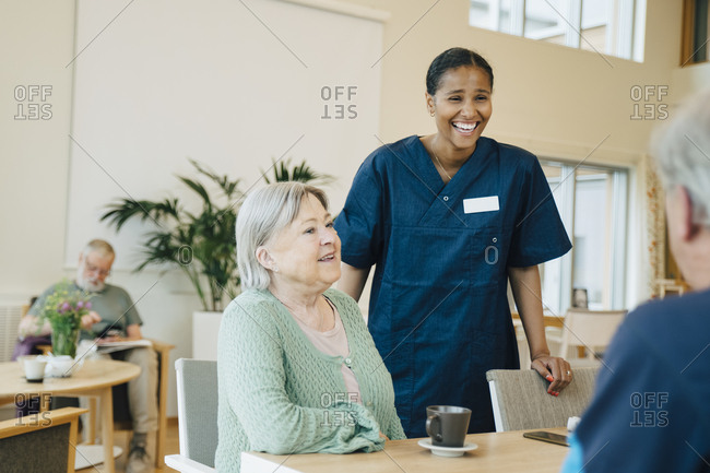 Cheerful young female nurse standing by senior woman while looking at man in retirement home