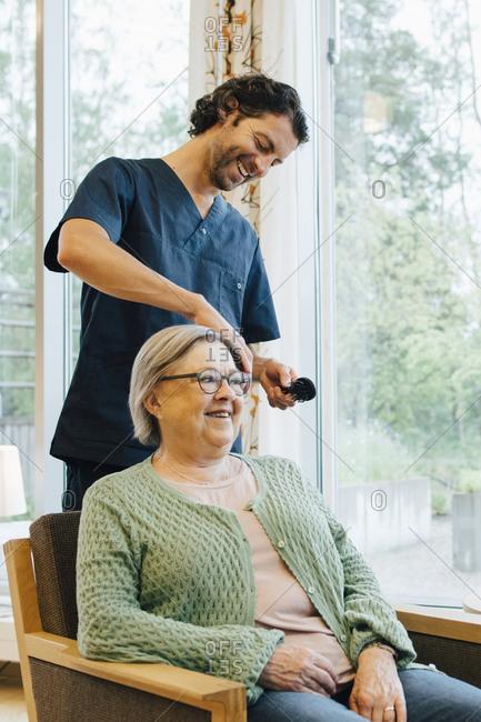 Smiling male nurse brushing senior woman's hair at retirement home