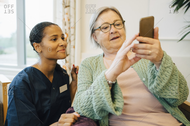 Smiling female caretaker looking at senior woman using mobile phone in nursing home