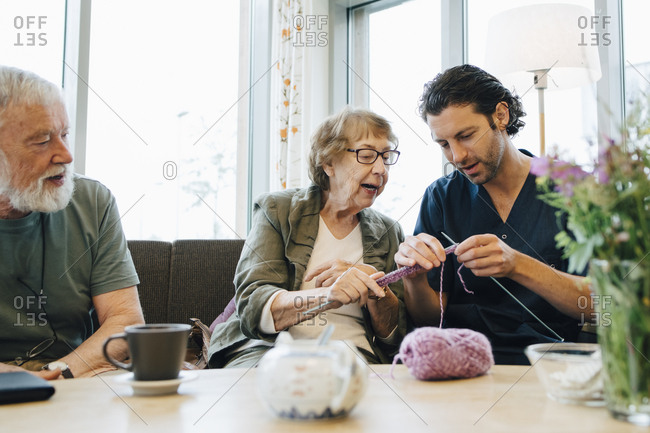 Retired senior woman teaching knitting to male nurse while sitting on sofa at elderly care home