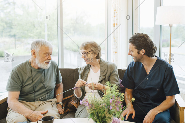 Smiling retired man and woman talking with male caregiver while sitting on sofa against window at nursing home