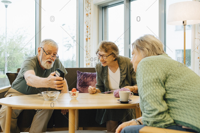 Retired elderly man sharing smart phone with friends sitting at table in nursing home